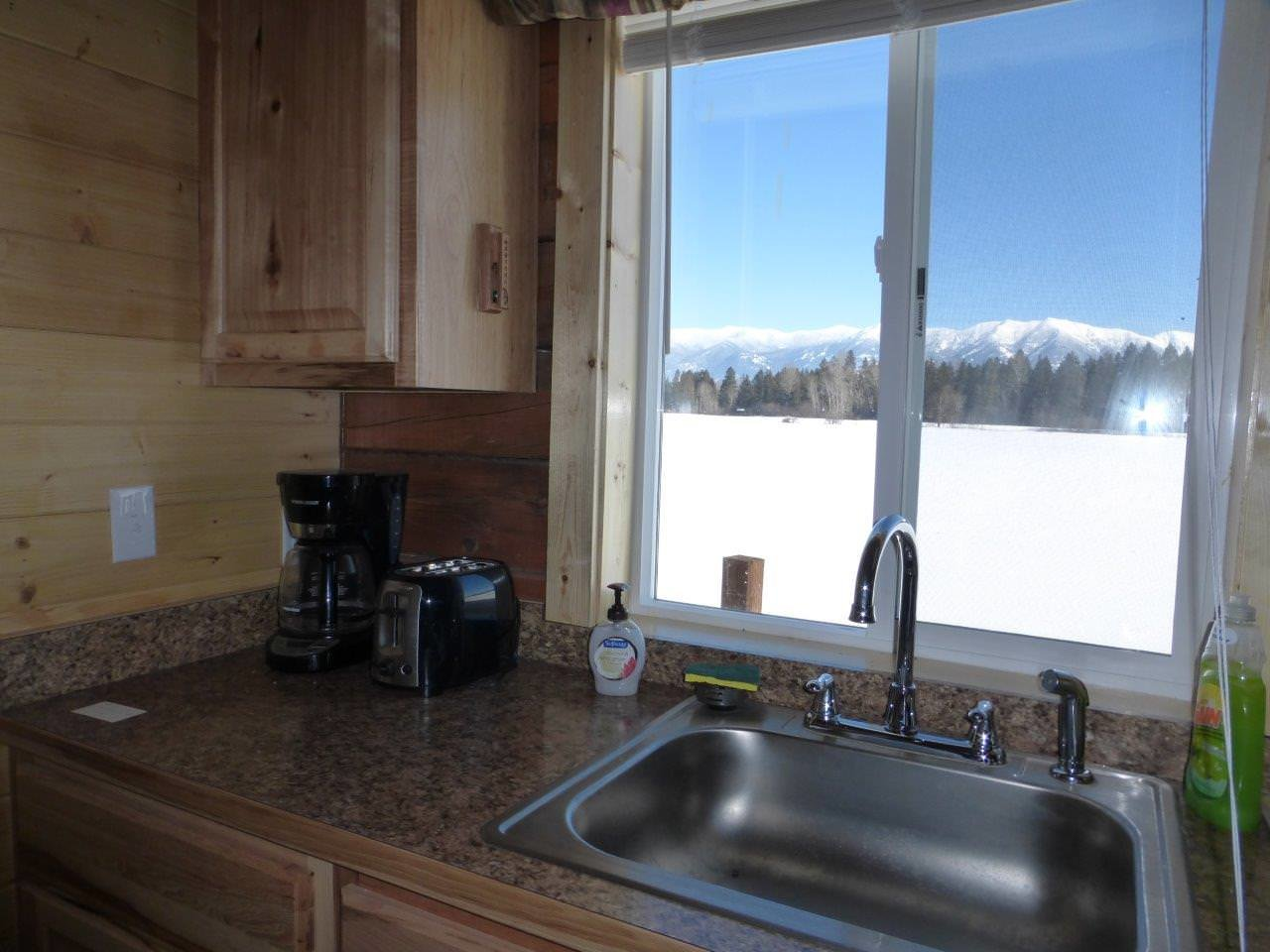 Sperry cabin kitchen overlooking mountains through window.